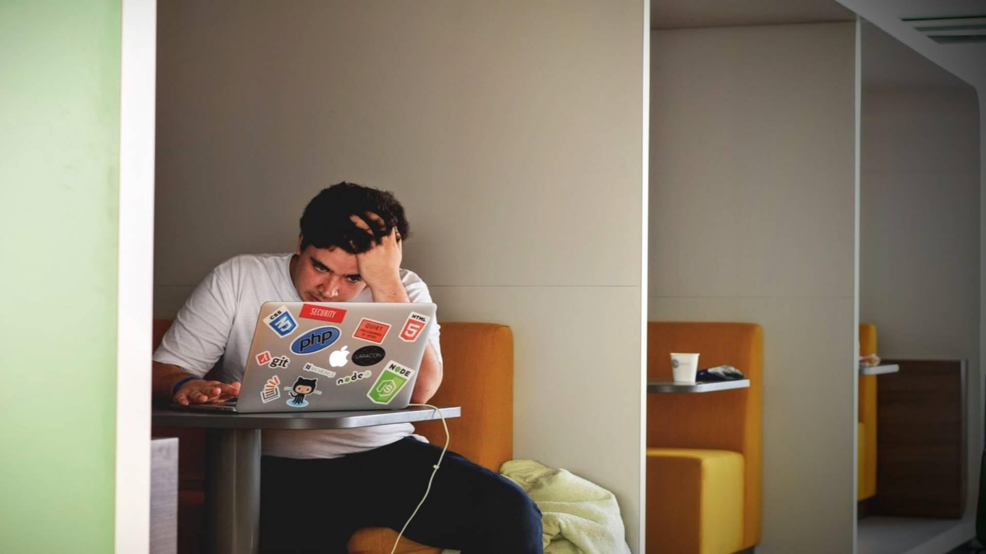 mężczyzna przed ekranem liczący stan zadłużenia