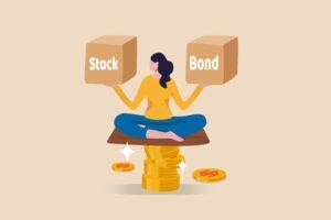 """Postać trzymająca pudełko z napisem """"akcje"""" i pudełko z napisem """"obligacje"""""""