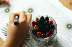 Dziecko rysujące kredkami świecowymi