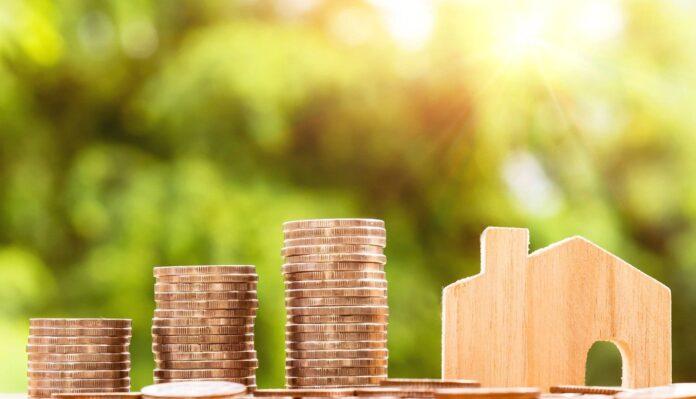 Coraz wyższe stosy pieniędzy i miniatura domu