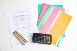 Umowa kredytu, teczki na dokumenty, długopisy i kalkulator