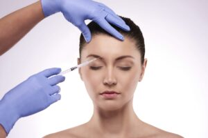 chirurg wstrzykuje botoks w czoło klientki