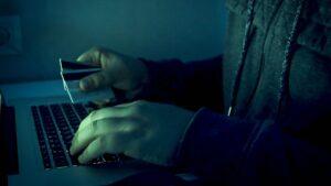 Pirat komputerowy piszący na klawiaturze do laptopa