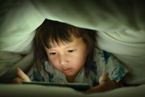 Dziecko korzystające z tabletu pod kołdrą