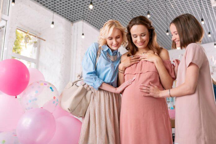 Uśmiechnięta kobieta w ciąży w towarzystwie koleżanek