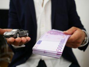 Mężczyzna trzymający w dłoniach banknoty i model auta