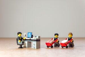 Figurka Lego inwestująca przed komputerem i dwie kolejne figurki przynoszące pieniądze