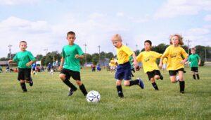 Dzieci rozgrywające mecz w szkółce piłkarskiej