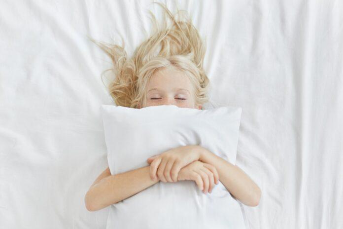 Śpiąca dziewczyna obejmująca poduszkę