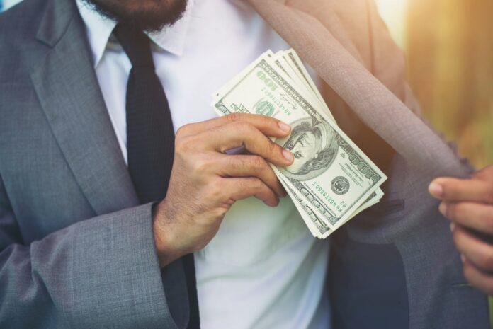 Mężczyzna chowający do kieszeni pieniądze otrzymane w ramach podwyżki