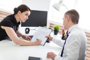 Mężczyzna dyskutuje z kobietą przed podpisaniem dokumentu dotyczącego poręczenia kredytu