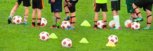 Piłki i pachołki na zajęciach w szkółce piłkarskiej