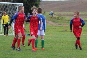 Młodzi zawodnicy grający mecz w szkółce piłkarskiej