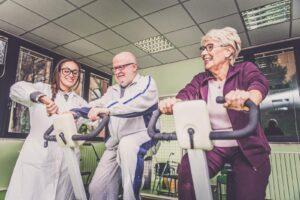 Dwójka seniorów ćwicząca na turnusie rehabilitacyjnym pod okiem specjalistki