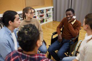 Grupa osób siedząca w kręgu na turnusie rehabilitacyjnym