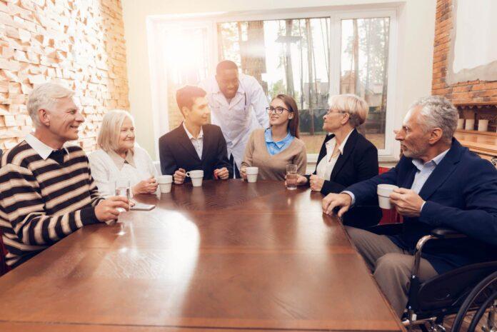 Grupa ludzi siedząca przy stole na turnusie rehabilitacyjnym