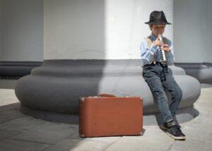 Dziecko ćwiczy grę na flecie przed wejściem do szkoły muzycznej