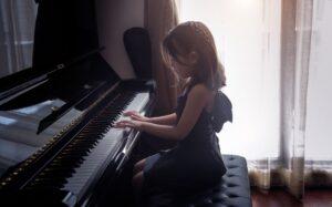 Dziewczynka gra na pianinie w szkole muzycznej