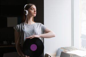 Kobieta w słuchawkach trzymająca płytę winylową