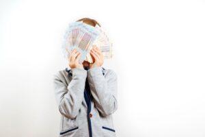 Dziecko z plikiem zaoszczędzonych pieniędzy