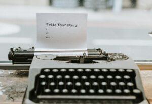 Maszyna do pisania z pierwszą strona zachęcającą do napisania własnej powieści