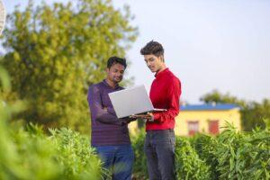 Ubezpieczyciel pokazujący rolnikowi warunki umowy na laptopie