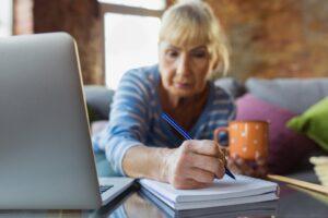 Kobieta notująca przepisy dotyczące limitów zarobkowych na wcześniejszej emeryturze