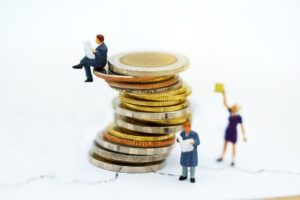 Miniaturowe postacie z książkami w otoczeniu monet