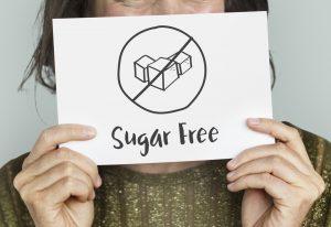 """Kobieta trzymająca kartkę z napisem """"bez cukru"""""""