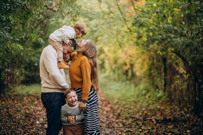 Szczęśliwa rodzina na jesiennym spacerze po lesie