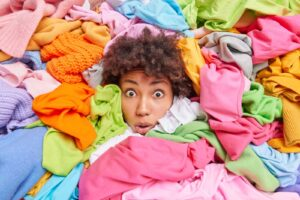 Kobieta borykająca się z nadmiarem ubrań