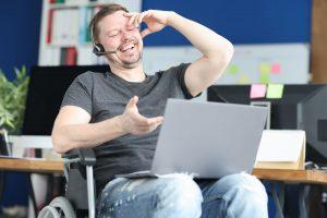 Uśmiechnięty niepełnosprawny w słuchawkach z laptopem na kolanach