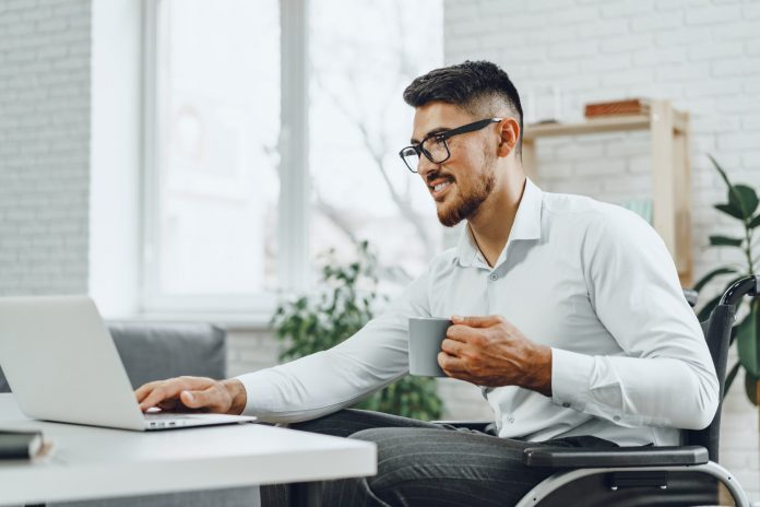 Uśmiechnięty niepełnosprawny pracownik w biurze