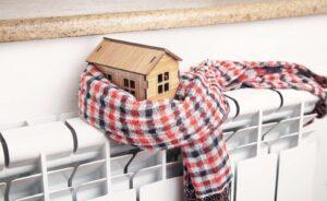 Model domu owinięty w szalik i stojący na kaloryferze