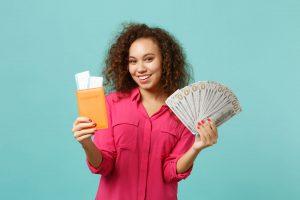 Kobieta trzymająca paszport i plik banknotów