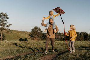 Ojciec z dziećmi puszcza latawiec jesienią