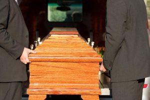 Żałobnicy niosący trumnę