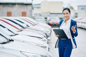 Sprzedawczyni prezentuje auta w komisie
