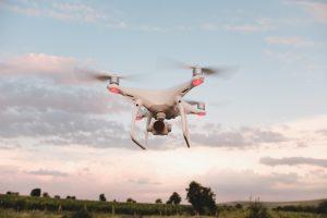 Biały dron z dużym obiektywem uchwycony w locie