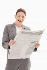 Inwestorka spoglądająca na notowania giełdowe w gazecie