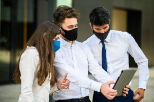 Biznesmen prezentujący swój pomysł na rozwijanie biznesu innym pracownikom w czasie pandemii