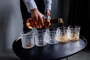 Kelner nalewa whisky do szklanek