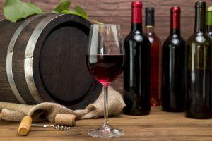 Kieliszek, butelki i beczka wina